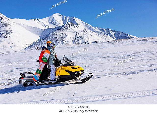 A group of snowboarders getting a ride up the hill on a snowmachine, Anaktuvuk Pass, Winter, Gates of the Arctic National Park, Brooks Range, Arctic Alaska