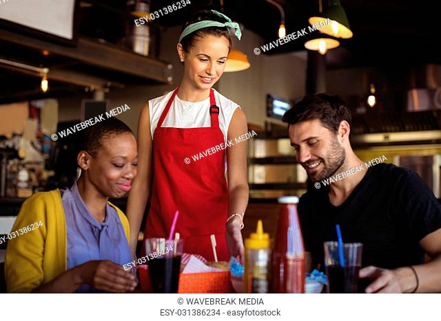 Waitress serving burger and french fries to customer