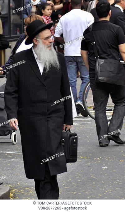 An elderly Jewish man walks down the streets of New York City