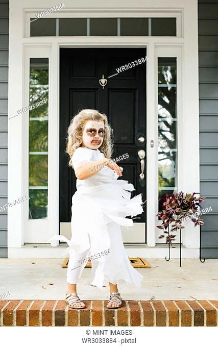 Portrait of blond girl dressed as ghost for Halloween, face painted white and brown