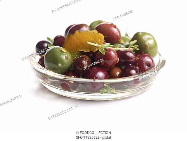 Black and green olives preserved in oil in a glass bowl