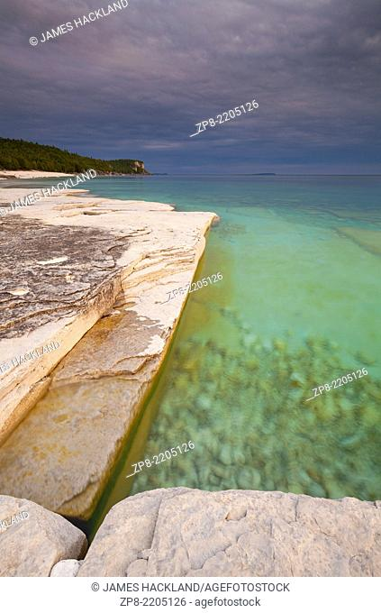 Interesting rock formations and crystal clear waters with an incoming storm. Bruce Peninsula National Park, Ontario, Canada