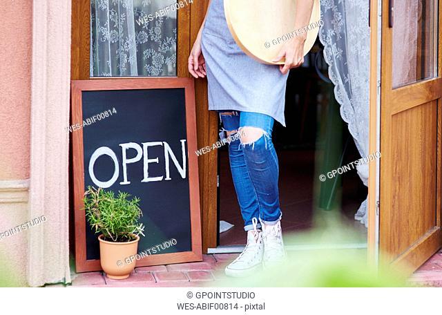Woman standing at open door of acafe