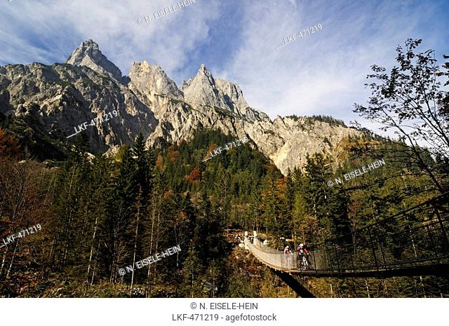 Mountain bikers passing chain bridge crossing Klausbach valley, Muehlsturzhoerner in background, Ramsua, Berchtesgadener Land, Upper Bavaria, Germany