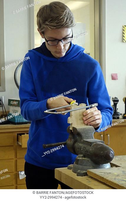 8th Grade Boy Using Coping Saw in Technology Class, Wellsville, New York, USA