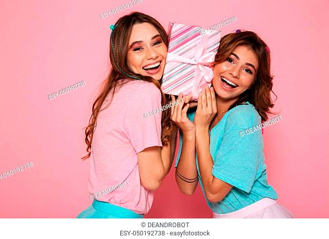 Two happy brunette woman in colorful tshirts holding gift box between their cheeks, looking at camera, isolated on pink background