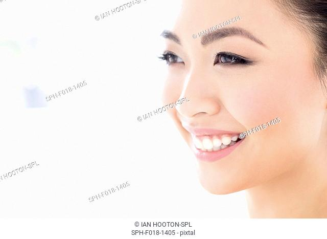 MODEL RELEASED. Young Asian woman looking away smiling, portrait