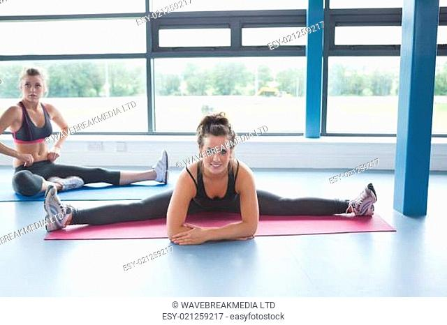 Woman stretching on a mat in gym