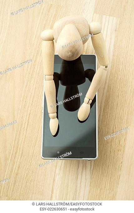 Wood doll with mobile phone. Concept of messaging, communication and technology lifestyle
