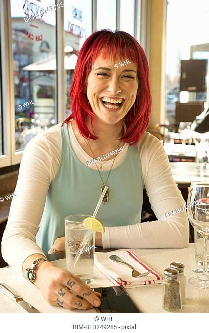 Caucasian woman laughing in restaurant