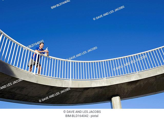 Caucasian runner resting on elevated walkway