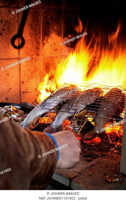 Man cooking fish in open fire