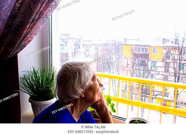Old lonely woman sitting near the window in his house and looking at camera