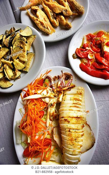 Typical food from Malaga at Restaurante Victoria on Palo beach: fried aubergines, fried red mullets, red peppers salad and grilled squid