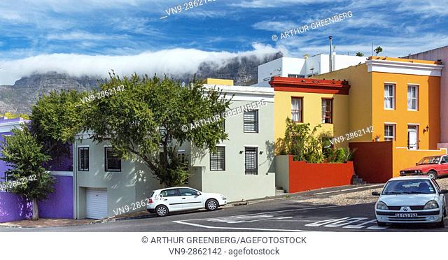 Cape Town, South Africa - 13 May 2015: Typical brightly colored Bo Kaap houses at corner of Pentz & Waal Streets below Tabletop Mountain
