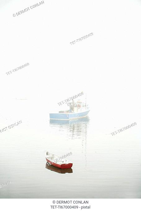 Boats in fog floating on water