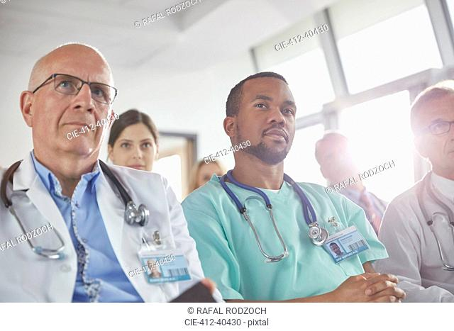 Attentive surgeons, doctors and nurses listening in meeting