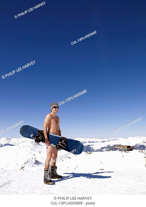 naked man holding snowboard on mountain