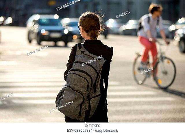 Young woman with backpack crossing the road at pedestrian crosswalk, walking in sunny European city street in summer, blurred cars and bicyclist on the...