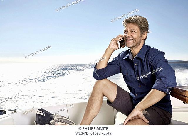 Portrait of smiling mature man on the phonesitting on his motor yacht
