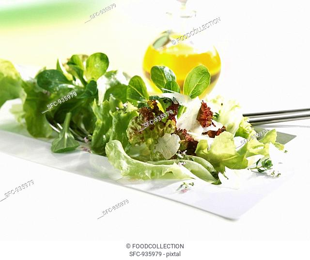 Mixed salad with Parmesan, bottle of oil in background