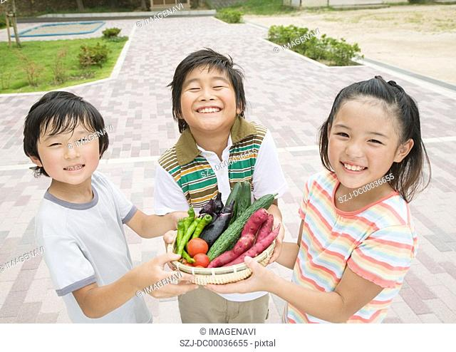 Elementary students holding vegetable