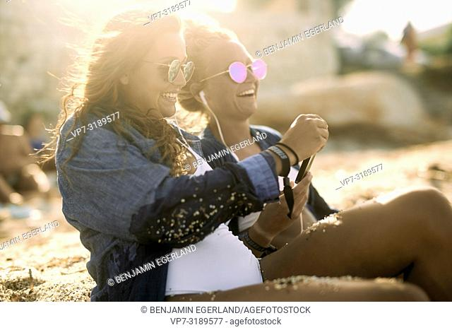 Two women relaxing at beach, listening music with smartphone. Chersonissos, Crete, Greece
