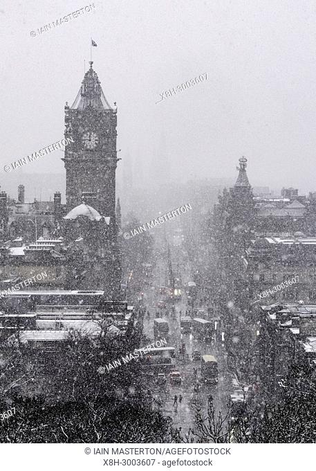 Snow falls on city of Edinburgh in December. Skyline view of city towards Princes Street from Calton Hill