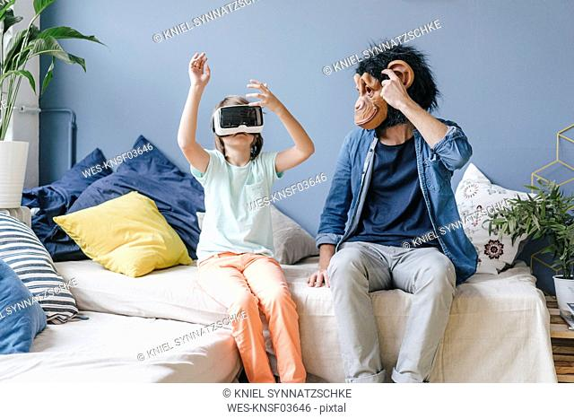 Father wearing monkey mask looking at son wearing VR glasses at home
