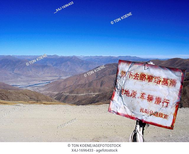 Warning sign in Chinese of dangerous road situations Road between Lhasa Tibet and Nepal