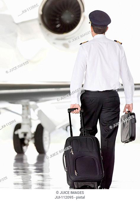 Pilot walking towards private jet with suitcase