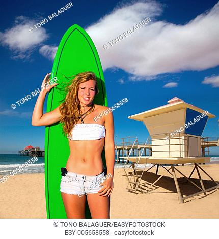 Blond surfer teen girl holding surfboard in Huntinton Beach pier California