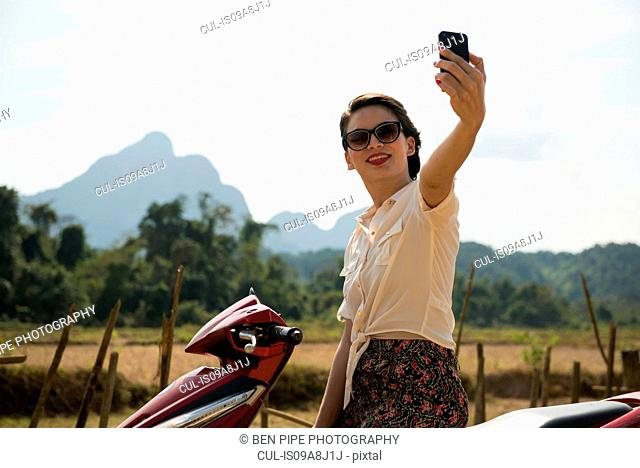 Woman photographing self on moped, Vang Vieng, Laos
