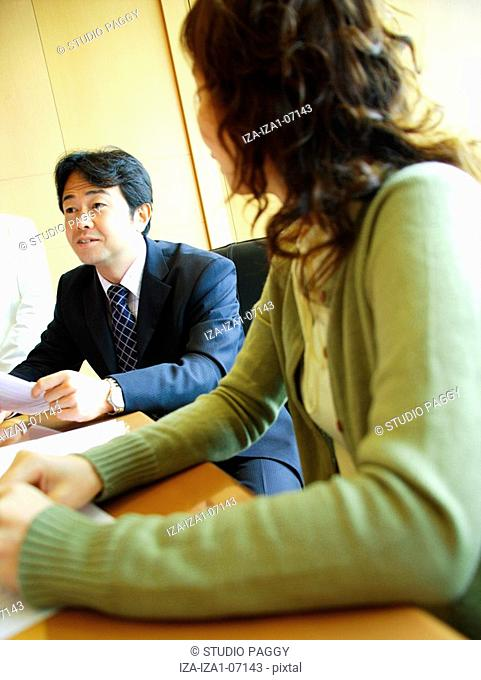 Businesswoman sitting at a conference table with a businessman discussing in a meeting
