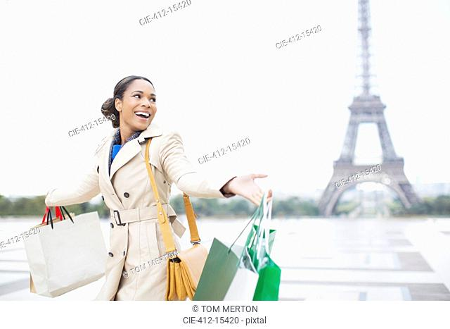 Woman carrying shopping bags by Eiffel Tower, Paris, France
