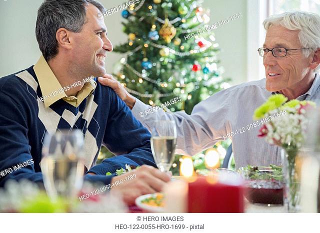 Senior man and son sitting around Christmas dinner table