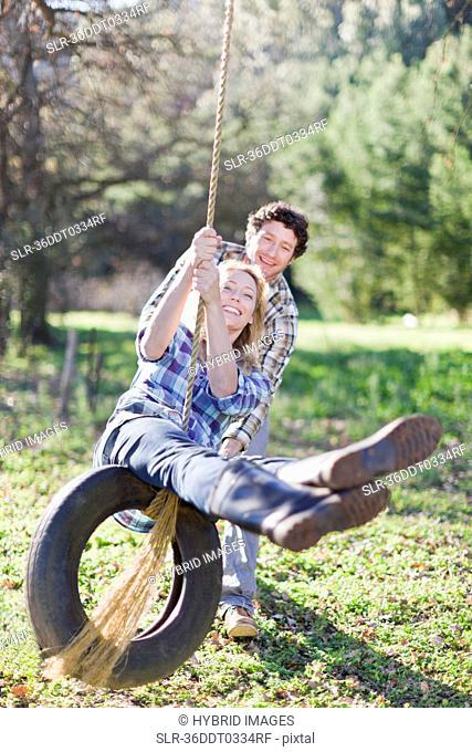 Man pushing girlfriend on tire swing