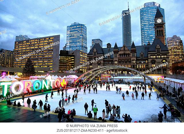 December 17, 2018 - Toronto, Ontario, Canada - People enjoy ice skating at an outdoor ice rink in Nathan Phillips Square in downtown Toronto, Ontario, Canada