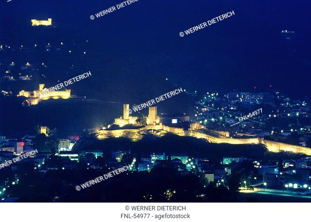 Castles lit up at night in city, Castellgrande, Castello Montebello, Sasso Corbaro, Bellinzona, Tessin, Switzerland