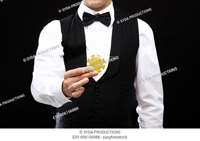 magic, performance, circus, casino and show concept - casino dealer holding golden poker chip
