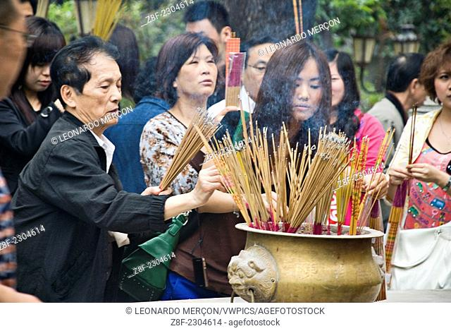 Women lightening incense in the Wong Tai Sin Temple in Kowloon, Hong Kong, China