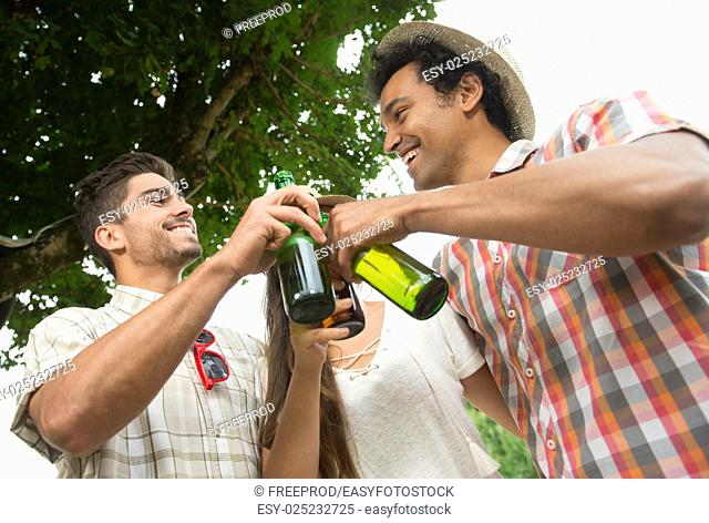 Group of friends toasting a beer bottle while preparing barbecue grill in park, France