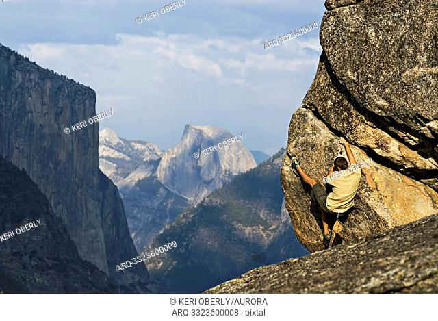 With Half Dome and El Capitan in the background, a young man is seen bouldering in Yosemite Valley, California