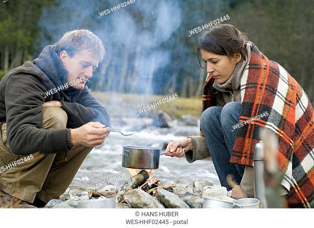 Austria, Salzburg County, Young couple at campfire