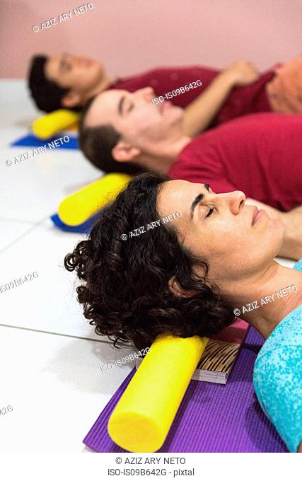 People at yoga class resting head on block