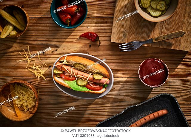 Hot dog with cucumber, lettuce, tomato, onion and cheese on wooden background. Fast food menu. Top view