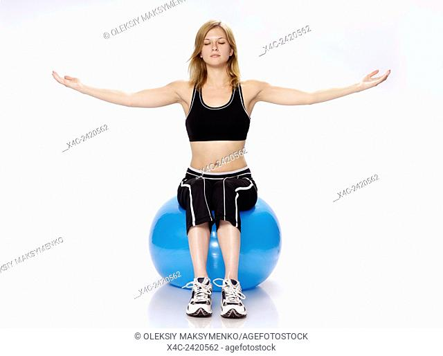 Young woman sitting on an exercising ball with closed eyes and her arms outstretched, balance, fitness, exercise concept