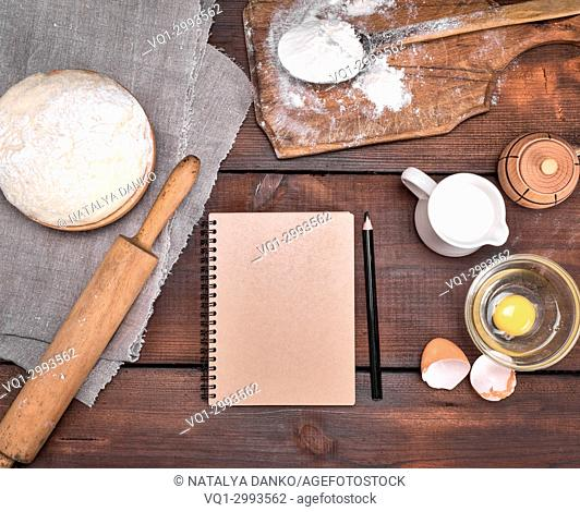 open blank notebook and black wooden pencil in the middle of the dough and ingredients for cooking, top view