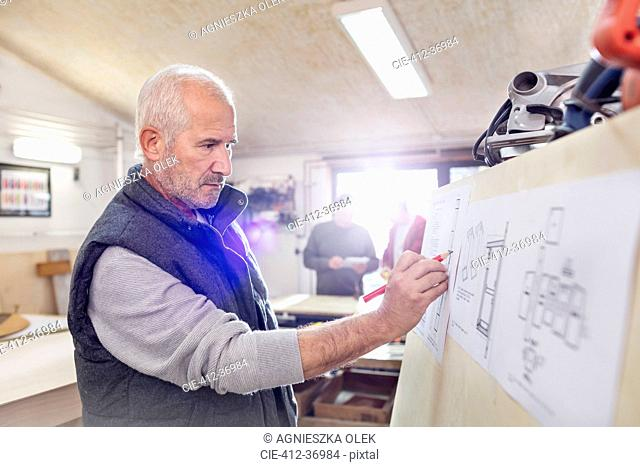 Senior male carpenter editing plans in workshop
