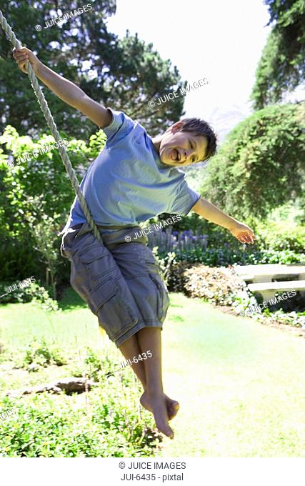 Boy 8-10 swinging on garden rope swing, arms out, laughing